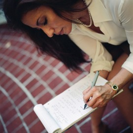 Woman Writing on Pad of Paper